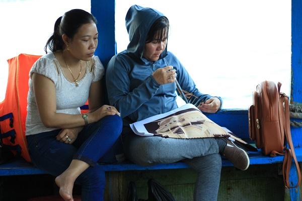 Phụ nữ xã đảo tranh thủ thêu tranh trong khi chờ tàu cập đất liền - Ảnh: Bông Mai