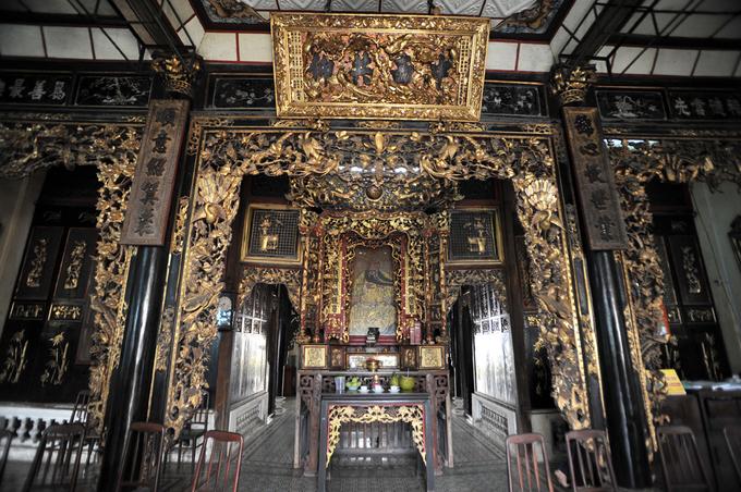 Nội thất căn nhà cổ mang đậm màu sắc Trung Hoa với cánh cửa, cột nhà, bàn thờ... sơn son thếp vàng, chạm trổ loan phượng rất sắc sảo và tinh tế. Chính giữa là ban thờ Quan Công, một vị tướng thời Tam Quốc.