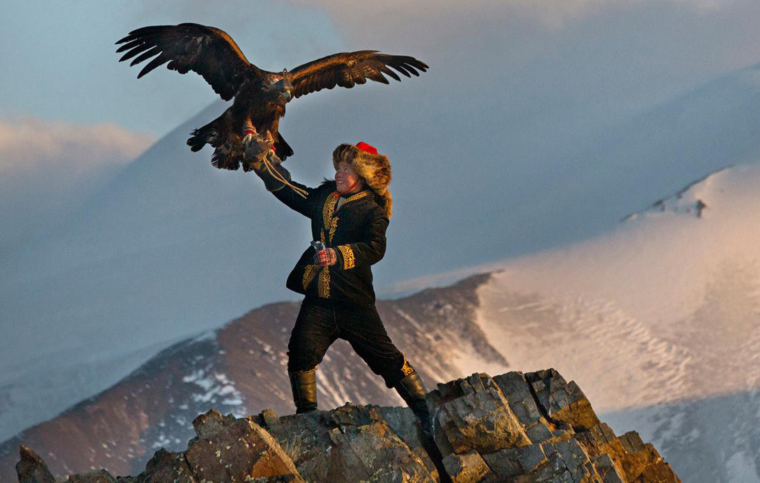Cô bé Aisholpan Nurgaiv với tay nâng cao một con đại bàng khổng lồ giữa không gian. Ảnh do Asher Svidensky chụp năm 2013
