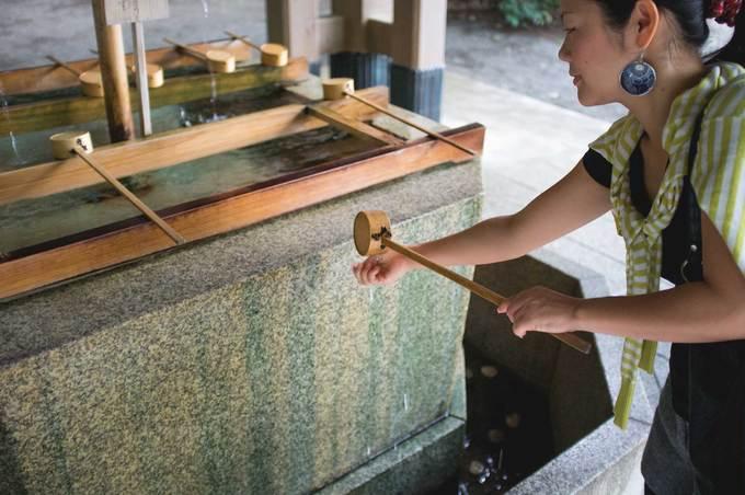"""Sau đó bạn phải """"tẩy trần"""" trước khi vào đền bằng cách dùng một muỗng tre lấy nước rửa tay trái rồi rửa tay phải, sau đó đổ nước lên tay trái để rửa miệng, rồi rửa lại tay trái, cuối cùng rửa sạch muỗng và đặt lại chỗ cũ. Lưu ý không được dùng miệng uống nước từ vòi, muỗng tre, cũng không được ném tiền xu vào đây."""