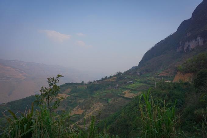 """Theo chân chú Thân, nhiếp ảnh gia ở Đồng Văn, tôi đến làng Mã Pắng hay còn gọi là làng Thiên Hương. Đường vào làng, một bên là vách núi, một bên là vực thẳm. Những ngọn núi cao lên tít tận trời mây khiến tôi nghĩ nó là """"cổng trời"""" của Đồng Văn. Khi phóng tầm mắt nhìn ra xa, thu vào là những con đường nhỏ nằm trên ụ núi.  Tôi nghe người bản địa bảo sông Nho Quế chạy từ Trung Quốc, rồi đi qua Lũng Cú và đoạn đường vào làng Thiên Hương chính là thượng nguồn của nó."""