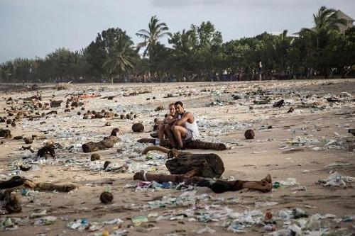 Du khách ngồi giữa bãi biển ngập rác. Ảnh: Independent.