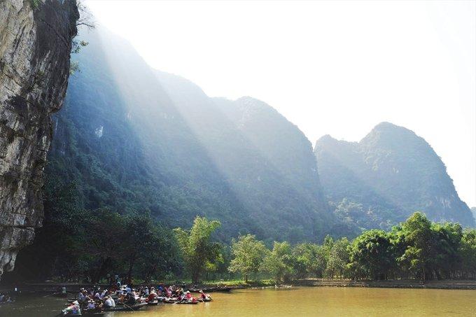 """Tam Cốc - Bích Động  Nằm ở xã Ninh Hải, huyện Hoa Lư, Tam Cốc - Bích Động là một điểm đến quen thuộc nhưng chưa đi thì coi như chưa tới Ninh Bình. Tam Cốc có nghĩa là """"ba hang"""", gồm hang Cả, hang Hai và hang Ba. Cả ba hang đều được tạo thành bởi dòng sông Ngô Đồng chảy xuyên qua các dãy núi đá vôi cao sừng sững.  Hành trình đi thuyền Tam Cốc dài 2 tiếng sẽ cho du khách tận hưởng khung cảnh thanh bình của núi non, những ruộng lúa nước, đặc biệt vào hè cũng là dịp lúa chuẩn bị chín vàng. Ngoài ra, du khách có thể leo núi tham quan chùa Bích Động - """"nam thiên đệ nhị động"""". Vé tham quan 120.000 đồng một người lớn, 60.000 đồng một trẻ em, và vé đò là 150.000 đồng chở được 4 người. Ảnh: Hương Chi."""