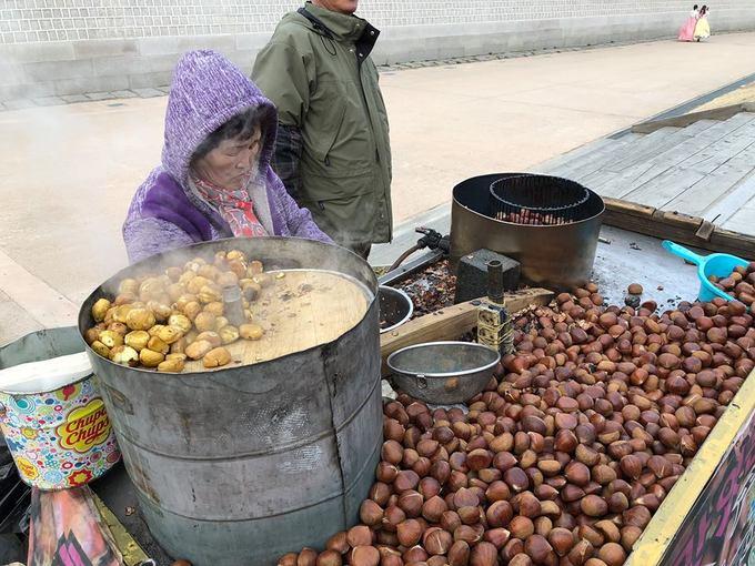 """Nếu đi ngắm hoa anh đào mùa này thì hạt dẻ rang thơm lừng của các cụ già bên vệ đường là món """"lương khô"""" không thể thiếu cho những buổi đi dạo của bạn. Một bịch nhỏ khoảng 5.000 won (khoảng 100.000 đồng), hạt to, tươi, thơm bùi nóng hổi sẽ khiến bạn thích thú."""