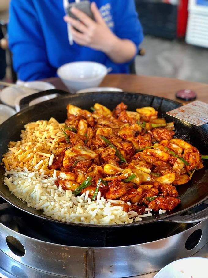 """Gà cay phô mai là một trong những món bạn nên thử khi đến Hongdae - một trong những khu sinh viên nổi tiếng nhất Seoul. Đồ ăn ở đây khá phong phú, giá cả hợp túi tiền sinh viên nên hàng quán luôn đông khách. Một số tiệm ở Hàn Quốc đếm đầu người để phục vụ nên khi chảo gà lớn được bê lên, anh chàng thầm nghĩ rằng mình sẽ không thể nào """"xử lý"""" hết. Tuy nhiên cuối cùng chảo gà đã """"bốc hơi"""" nhanh gọn."""
