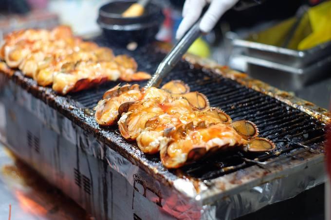 """Nhiều người không thể rời mắt khi lỡ đi ngang hàng bán tôm nướng phô mai ngay khu mua sắm Myeongdong được. Những con tôm tươi """"đắp"""" đầy phô mai, nằm xếp lớp trên bếp than hồng tỏa hương thơm khắp phố làm ai cũng phải dừng bước. Tuy nhiên với giá 15.000 won/con (khoảng 300.000 đồng) sẽ khiến bạn cân nhắc trước khi móc ví."""