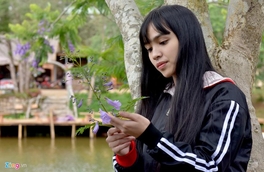Cô gái trẻ nâng niu say lòng bên hoa phượng tím. Măng Đen hội tụ nhiều điều kiện khí hậu, không gian rừng nguyên sinh, danh lam thắng cảnh... để phát triển trở thành trung tâm du lịch sinh thái và nghỉ dưỡng cấp quốc gia.
