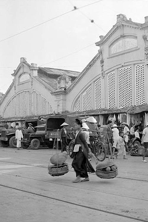 Một phụ nữ gánh hàng trước chợ đầu thập niên 1950. Ảnh: Flickr.