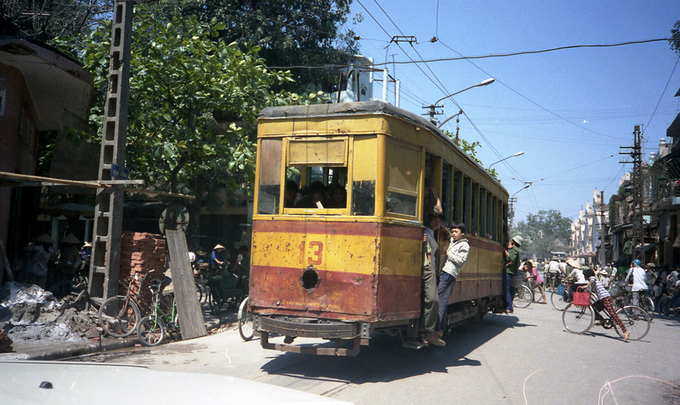 Tàu điện trên phố Đồng Xuân. Phía sau về bên phải ảnh là chợ Đồng Xuân với 5 gian. Ảnh: Flickr.