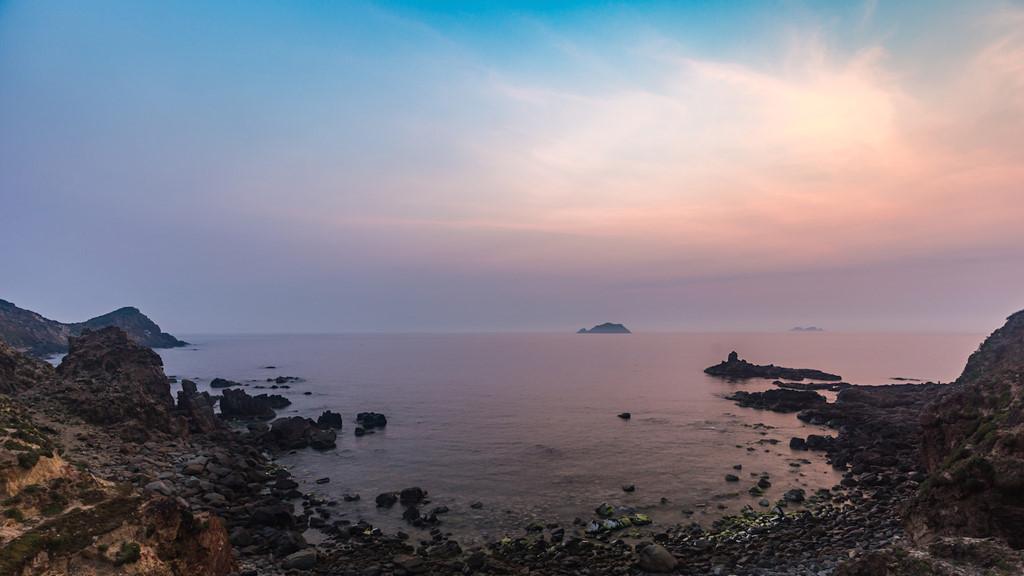 """Được mệnh danh là """"nơi ngắm bình minh đẹp nhất Việt Nam"""", những ai một lần đến Eo Gió sẽ không thể bỏ lỡ khoảng khắc bình minh ló rạng. Thời điểm này, Eo Gió đẹp ngỡ ngàng với những vệt sáng hồng kỳ ảo soi chiếu, lan toả dập dìu trên sóng nước mênh mông."""