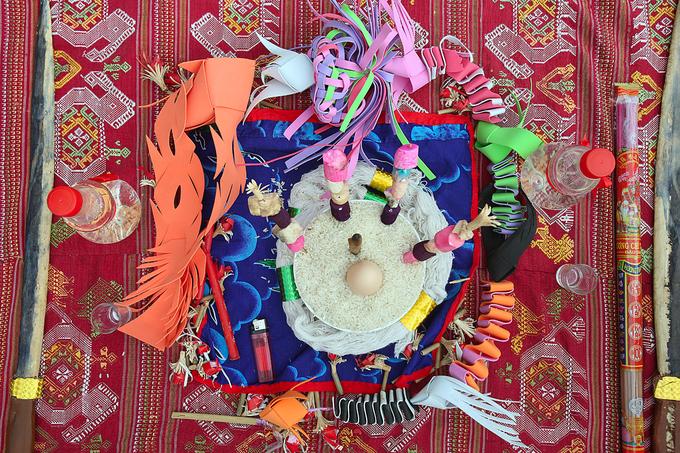 Mâm lễ của thầy mo được chuẩn bị riêng, gồm rượu, hai thanh đao dài, hương, nến, cơm và nhiều con vật sắc màu làm thủ công bằng tay giống trang trí trên cây boọc.