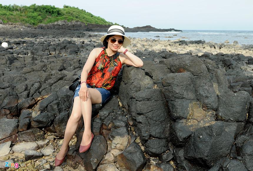 """Du khách tạo dáng bên bãi đá trầm tích núi lửa muôn hình kỳ thú. """"Tôi đi du lịch nhiều nơi, nhưng chưa nơi nào ở Việt Nam có bãi trầm tích núi lửa, dải san hô trải rộng khắp nơi hấp dẫn như vùng ven bờ ở Gành Yến. Vợ chồng tôi thích nhất là thuê ghe thúng ngắm đàn chim yến bay về tổ bên vách đá núi lửa nơi đây cảm giác yên bình thật tuyệt vời """", Chị Trần Thị Hằng (du khách đến từ TP HCM) chia sẻ."""