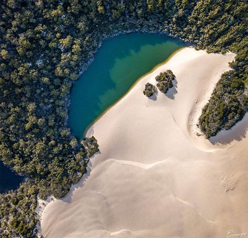 """Chính quyền bang Queensland mới đây khởi động chiến dịch quảng bá du lịch """"Tuyệt vời hôm nay, hoàn hảo ngày mai"""" cùng thời điểm diễn ra Hội thảo Thịnh vượng chung Gold Coast, theo Escape.  Hồ Wabby, đảo Fraser  Nằm ở sườn phía nam của K'Gari (đảo Fraser), hồ Wabby là một kỳ quan bị lãng quên. Đụn cát trải dài dọc bờ đang dịch chuyển ra phía hồ một mét mỗi năm và cuối cùng sẽ nuốt chửng mặt hồ. Hồ Wabby là nơi cư ngụ của 12 loài cá hiếm, trong đó có loài """"mắt xanh mật ong""""."""