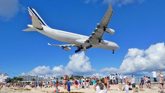 """9. Sân bay St Maarten, Hà Lan  Sân bay nổi tiếng St Maarten được biết đến với bãi biển đông người nằm ngay sát đường băng. Nếu kiên nhẫn bạn sẽ có một bức ảnh để đời tại đây. """"Không có mấy nơi trên thế giới vừa có biển, có nắng, có du khách và cả máy bay ngay trên đầu nữa"""", một người viết."""