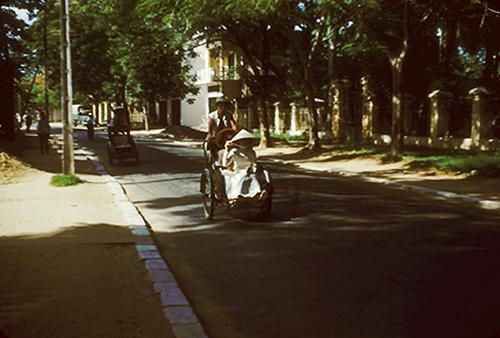 Một góc đường Đà Nẵng với nhiều cây cối rợp bóng mát, xe xích lô là phương tiện được sử dụng phổ biến. Những năm đầu thập niên 50 cũng là thời điểm Pháp rút khỏi Đà Nẵng.