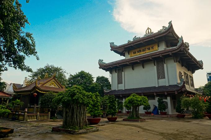 """Phía sau chùa là khu chánh điện với dòng chữ """"Nam thiên nhất trụ tự"""". Quanh chánh điện là khu vườn cây cảnh, có những cây tuổi đời cả trăm năm."""