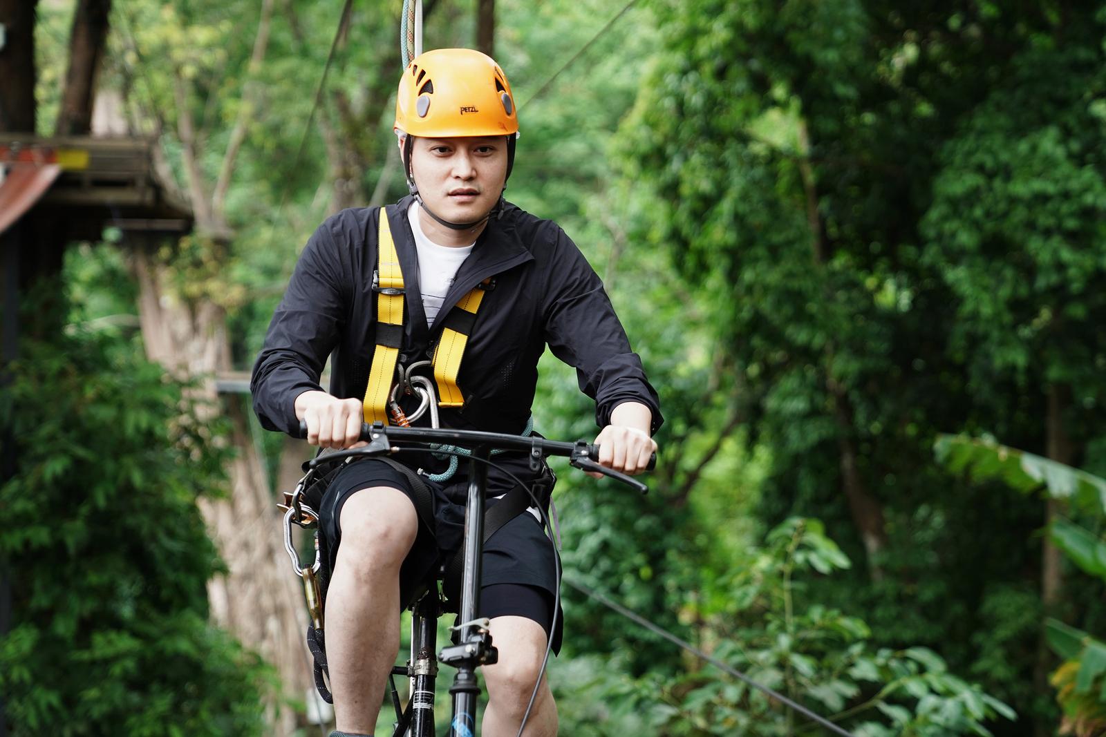 Ca sĩ Quang Vinh thử sức với trò đạp xe đạp trên dây băng qua vực sâu. Ảnh: Nguyễn Minh Tuấn.