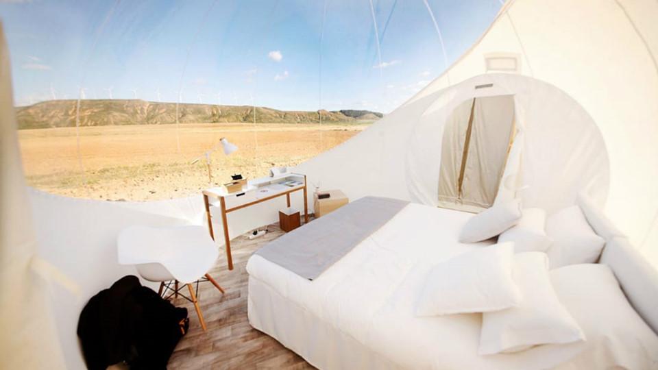 4. Aire de Bardenas (Tây Ban Nha): Khách sạn này nằm ở Đông Nam Navarre, bên rìa công viên Bardenas Reales, hai bên là mỏm đá sa thạch và cánh đồng lúa mì. Các lều bong bóng mang vẻ đẹp nhẹ nhàng với phong cách trang trí tối giản, lấy màu trắng làm màu chủ đạo, nhường toàn bộ sự nổi bật cho cảnh quan tuyệt đẹp xung quanh. Chi phí thuê phòng bong bóng thấp nhất là 325 USD/đêm. Ngoài ra, những du khách không thích sống trong căn phòng trong suốt có thể lựa chọn phòng khách sạn truyền thống, sang trọng với các bồn tắm nước nóng ngoài trời.