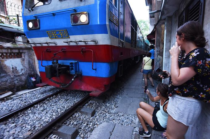 Các du khách ngồi đợi đến giờ tàu chạy để chụp ảnh, quay video và trải nghiệm cảm giác mạnh khi ngồi sát con tàu lao qua.