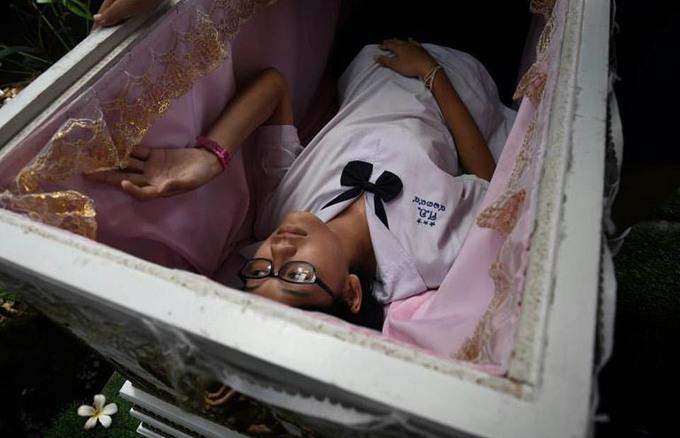 """Những người dám chui vào quan tài sẽ được giảm giá đồ uống.  """"Tôi có cảm giác như mình đang đến một đám tang vậy"""", Duanghatai Boonmoh, 28 tuổi, vừa cười vừa nói khi cô đang nhấm nháp một viên kẹo có tên """"tử thần""""."""