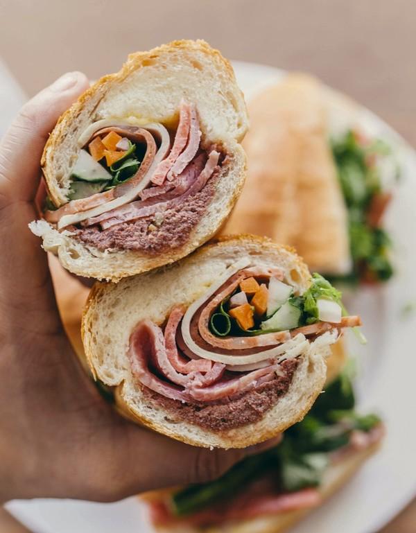 Bánh mì ở Cô Thành được nhiều thực khách quốc tế yêu thích bởi đầy đặn với đủ pate, thịt nguội, tương ớt, mayonnaise, rau thơm, dưa chuột. Thực khách muốn ăn bánh mì nên tới sớm để có thể đảm bảo bánh của mình nóng và giòn hơn. Ảnh: SCMP.