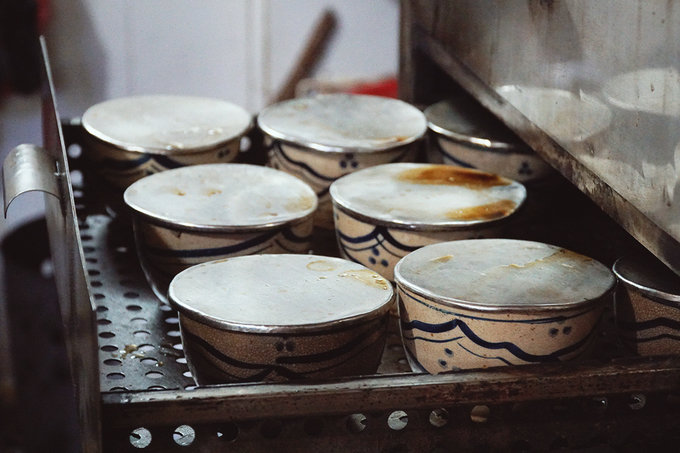 """Để đảm bảo vị chuẩn của món ăn, sau khi tiềm lần đầu, đầu bếp sẽ chia nước thuốc bắc và gà vào hai nổi riêng để tiềm một lần nữa. """"Gà chín vừa tới thì vớt ra thố nhỏ. Khi có khách gọi món, những thố đất này sẽ được hấp lại cho nóng"""", anh Thành nói."""