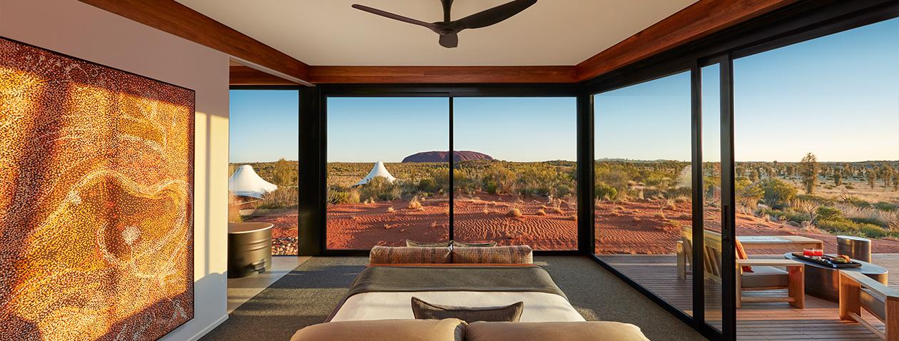 """Longitude 131 - Uluru, Northern Territory (Australia)  Longitude 131 là nơi tuyệt vời để bạn có thể ngắm hòn đá Uluru linh thiêng của người Anangu Pitjantjatjara (Australia). Đây là khách sạn gần hòn đá 600 triệu năm tuổi nhất, bạn có thể ngắm nó từ trên giường ngủ với tầm nhìn không bị chắn bởi bất kì thứ gì. Khi mặt trời lặn, bạn còn được chiêm ngưỡng quá trình đổi màu kì diệu của hòn đá, từ đỏ thẫm chuyển sang màu tím, đêm xuống thì khoác lên mình màu vàng nâu hòa với cảnh vật xung quanh. Nếu may mắn gặp trời mưa to, hay khi vừa tạnh mưa thì hòn đá khổng lồ lại có màu tro bạc, pha lẫn một chút đen kỳ thú. Sở hữu """"view vàng"""" khiến nó có giá tầm 37 triệu đồng/đêm."""