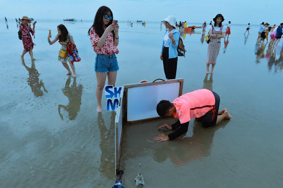 Để có mặt nước lặng như gương phản chiếu, các nhân viên du lịch đã phải chắn gió và nước, sau đó đắp cát để tạo bờ ngăn sóng.