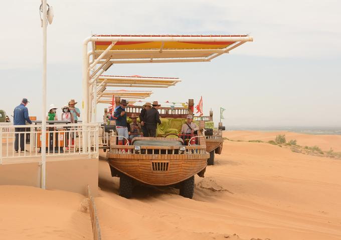 """Với vé trọn gói, khách sẽ được tham quan một vòng quanh sa mạc bằng """"phi thuyền"""". Đây thực chất loại ôtô chuyên dụng, được cải tạo với hình dáng phi thuyền, lướt tốc độ cao trên sa mạc. Trên con """"thuyền"""" đi như bay trong nắng gió sa mạc, bạn sẽ nhìn thấy cát ở đây đổi màu theo giờ, khi trắng, vàng, rồi chuyển sang hồng.  Là sa mạc nhưng nơi đây có khí hậu se lạnh vào mùa hè, cộng thêm gió lớn nên hầu hết khách đều phải mặc áo khoác. Theo hướng dẫn viên địa phương, cũng như thảo nguyên, cao điểm du lịch ở sa mạc là tháng 7, 8, khi thời tiết không quá lạnh."""