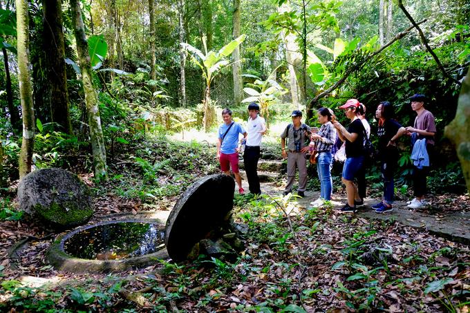 Mọi người được nghe kể chuyện về các loại cây, các di tích (trong hình là cối xay thời Pháp) trên đường di chuyển trong rừng.