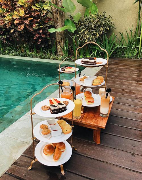 """Chàng trai rất hài lòng với tất cả các dịch vụ khách sạn được trải nghiệm ở Bali. """"Dịch vụ ở Bali siêu đỉnh! Cả nhà mình 5 người khi nhận phòng được chào đón bằng 3 tháp trà bánh siêu nhiều phục vụ tận nơi, ăn mãi mà không hết. Nhân viên thì lúc nào cũng tươi cười, lúc nào cũng cúi đầu chào khi nhìn thấy khách. Bữa sáng cũng được phục vụ tại phòng rất ngon, order từ tối hôm trước để họ chuẩn bị. Khi check out cũng được tiễn bằng 5 quả dừa cài hoa đại xinh ơi là xinh"""", Hoàng cho biết."""
