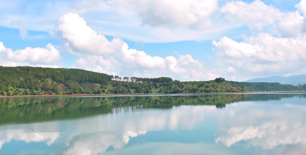 Mây và hàng cây soi bóng xuống mặt hồ