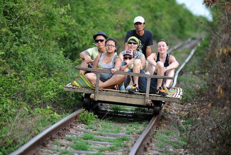 """Đi """"tàu lửa tre"""": Nghe như đùa, nhưng ban đầu, đây là phương tiện vận chuyển của người dân vùng ngoại ô hẻo lánh ở thành phố Battambang. Tuy thu hút nhiều du khách, song nó từng đóng cửa vào năm 2017 trước khi trở lại phục vụ du lịch quãng đường 20 km trong khu vực đền Banan. Ảnh: Camsocial.news."""