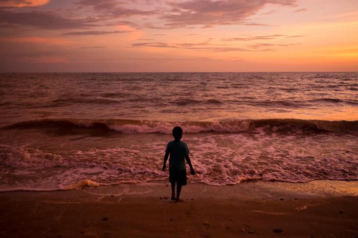 Cậu bé đứng trước bãi biển trong lúc hoàng hôn trên đảo Melville thuộc quần đảo Tiwi - Ảnh: DAVID MAURICE SMITH, OCULI/NG