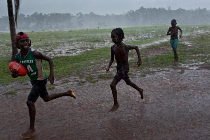 Một nhóm trẻ em chơi môn bóng đá kiểu Úc trong mưa tại khu dân cư Pirlangimpi, đảo Melville - Ảnh: DAVID MAURICE SMITH, OCULI/NG