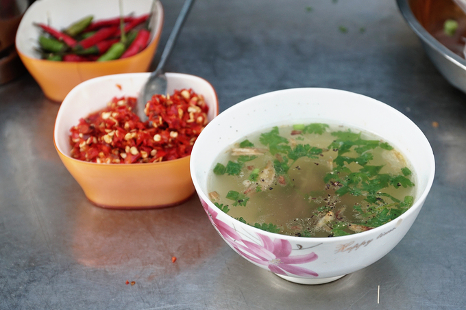 Chén nước súp được phục vụ kèm là nước luộc gà thơm lừng, có thêm chút hành phi và hành lá xắt nhuyễn, tỏa mùi hấp dẫn. Nhờ vậy, khách nào ăn chua không quen có thể húp một muỗng để vị chua trong miệng nhạt lại.