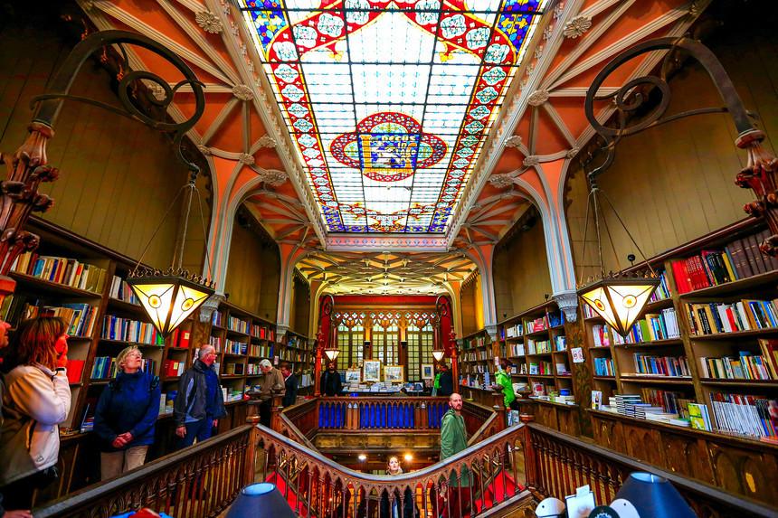 Trần nhà là tấm kính nhiều màu bắt mắt, ở giữa là logo của tiệm viết tên của người sở hữu. Ô cửa sổ lớn phía cuối phòng cũng được thiết kế tương tự, cùng các chùm đèn màu vàng tạo cảm giác ấm áp.