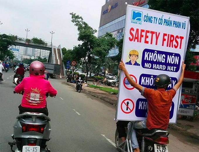 """Việt Nam cũng góp mặt trong bộ ảnh này. Khách Tây choáng váng với hai người đàn ông chở theo tấm bảng lớn cho chữ """"Safety first"""" (An toàn trên hết) nhưng lại theo cách không hề an toàn."""
