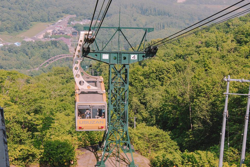 Một đường cáp treo trên núi Usu giúp mọi người có thể phóng tầm nhìn ra Showa-shinzan, một ngọn núi trẻ khác với đặc điểm dễ nhận biết là đỉnh núi màu đỏ đất. Để lên cao và ngắm nhìn núi Usu, bạn cần phải di chuyển bằng Usuzan Ropeway.
