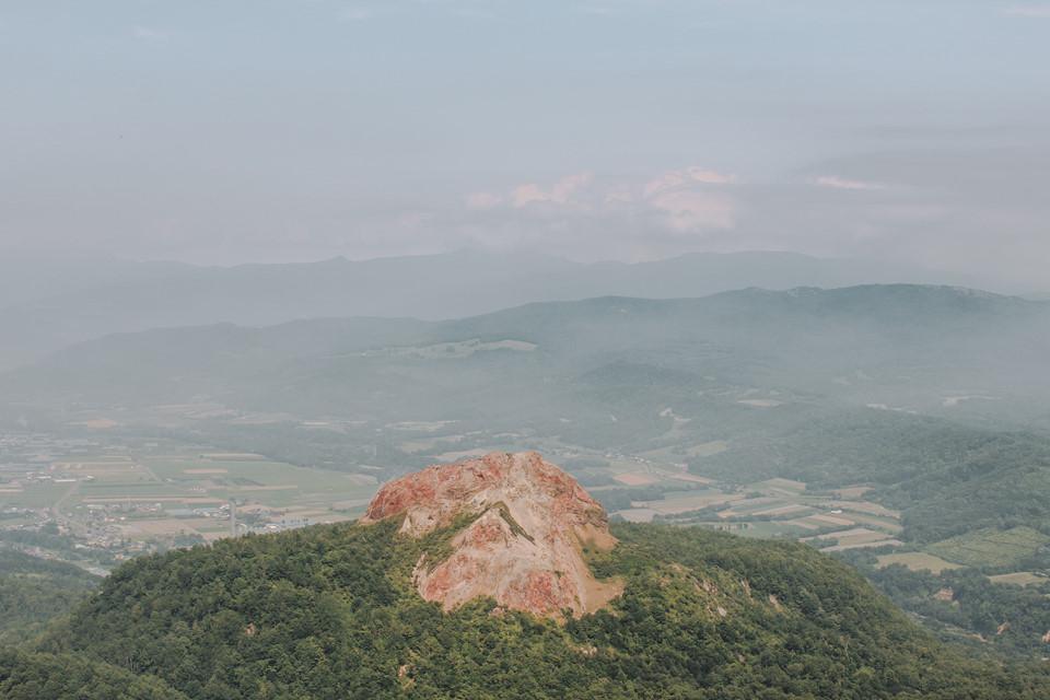 Tôi đi lên Usuzan Ropeway và tới trạm đầu chỉ sau gần 10 phút. Từ bên trong Usuzan Ropeway, tôi ngắm nhìn ngọn núi Showa-shinzan phía xa đang đắm mình bên dưới ánh mặt trời tháng 7.