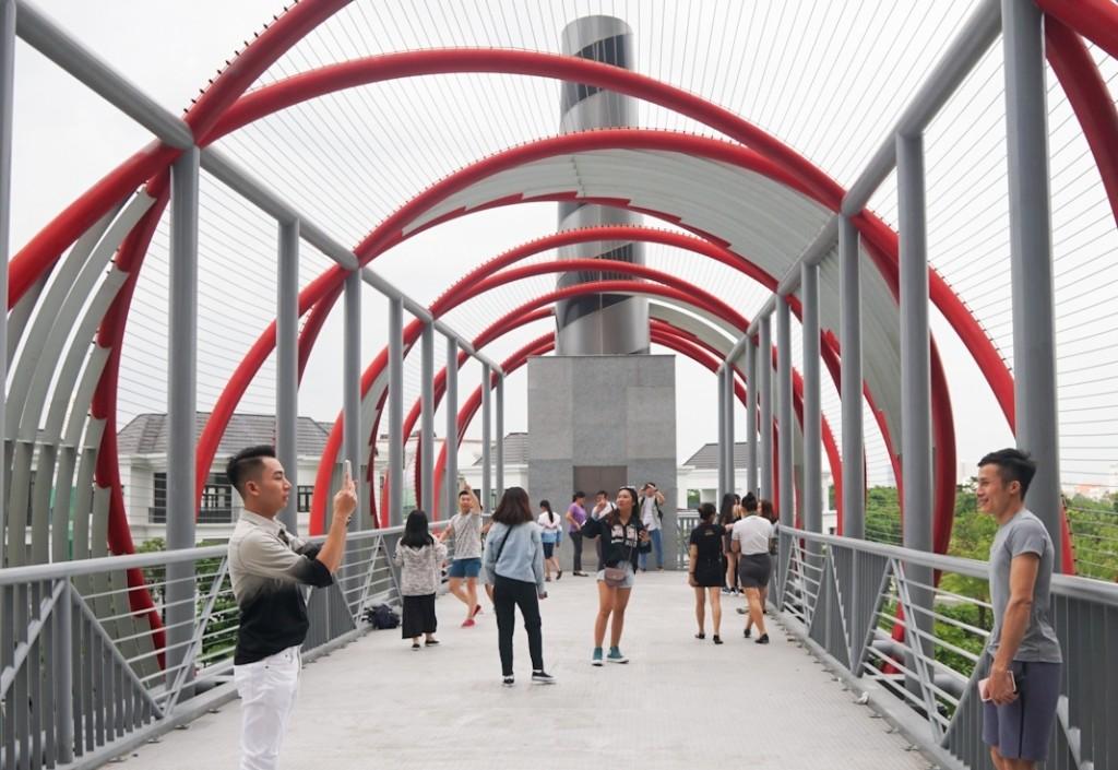 Bạn trẻ đua nhau chụp ảnh, check-in cho kịp xu hướng trên cầu đi bộ bên ngoài tòa nhà.