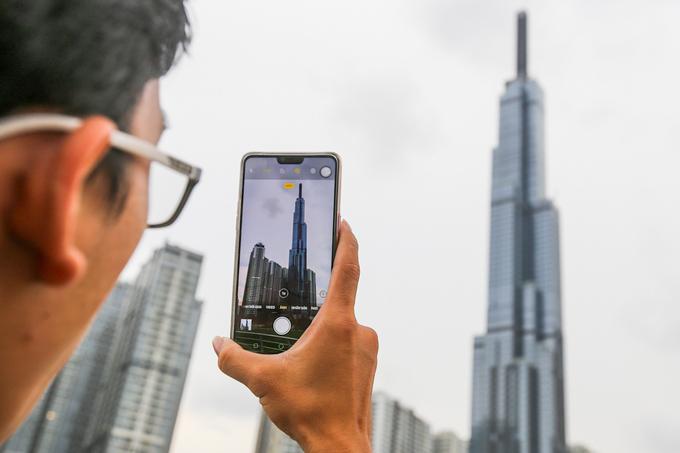"""Nhiều bạn trẻ tỏ ra hào hứng, thoải mái sáng tạo đủ kiểu ảnh với tòa nhà cao nhất Việt Nam. Góc """"sống ảo"""" với Landmark 81 rất đa dạng bởi đứng ở vị trí nào cũng có thể nhìn thấy tòa tháp."""