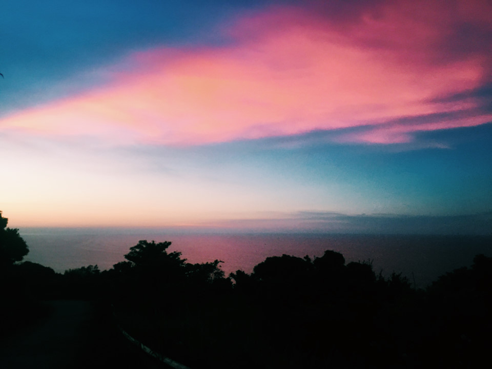 Hoàng hôn nhuộm hồng cả bầu trời, in bóng xuống mặt biển.