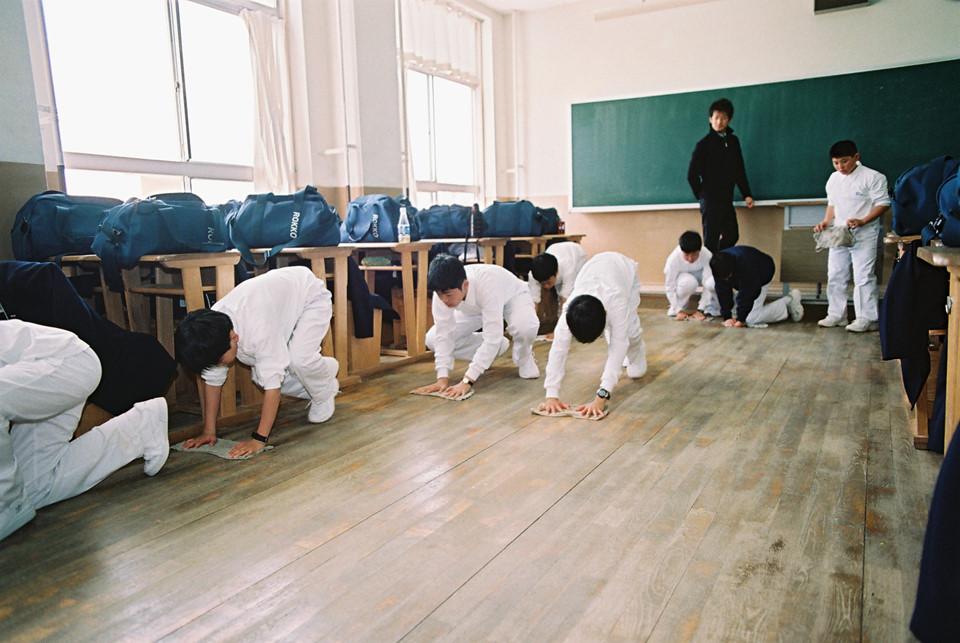 """Tinh thần chủ động từ nhỏ: """"Không phải ai khác sẽ làm, chúng tôi sẽ giữ gìn vệ sinh công cộng"""". Từ bậc tiểu học ở Nhật Bản, các ngôi trường đã giáo dục việc giữ gìn vệ sinh không gian chung cho các em nhỏ. Đến đại học, 12 năm liền học sinh được đào tạo, hướng dẫn tự giữ gìn vệ sinh trường học. Tính tự giác và nhận thức của học sinh Nhật Bản cao đến mức hầu hết trường đại học không cần thuê người giám hộ. Vào thời gian nghỉ trưa, tất cả học sinh, sinh viên tham gia dọn dẹp sân trường với niềm phấn khởi như kỹ năng lao động. Ảnh: FinancialTribune."""
