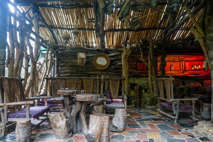 Không gian nhà dựng bằng tre nứa, những vật dụng như gùi, cồng, chiêng, chum, tượng... được trang trí khắp nơi trong quán.