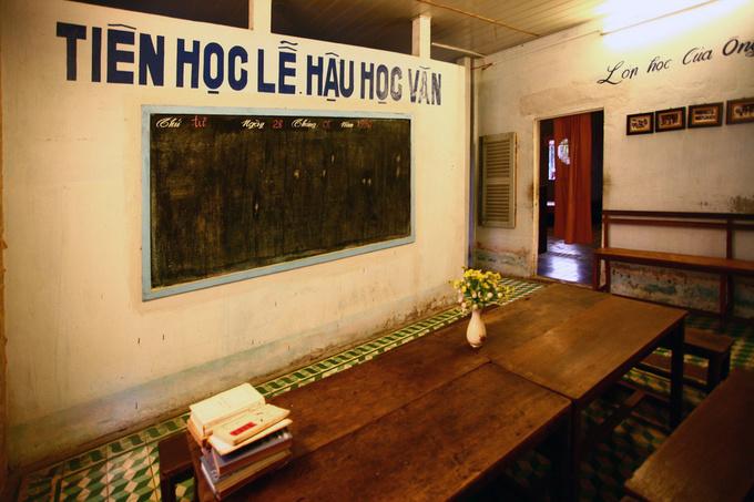 Phòng dạy học của ông giáo với tấm bảng đen và bàn ghế được kê gọn gàng.