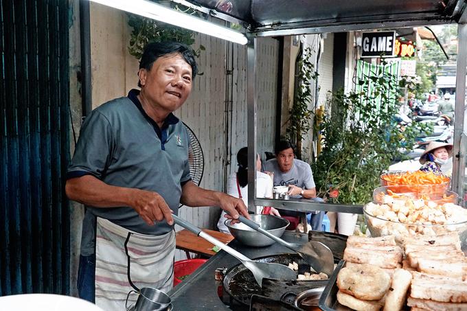 """Nằm gọn trong lòng một con hẻm thông giữa hai đường Võ Văn Tần và Nguyễn Thị Minh Khai (quận 3), quán bột chiên của anh Bảy và chị Chi được nhiều thực khách biết đến bởi đã có mặt ở Sài Gòn từ lâu.  Anh Bảy cho hay, quán được vợ chồng anh mở từ những năm 1990, khi những món ăn chơi ở thành phố chưa nở rộ như bây giờ. """"Từ đó đến nay chúng tôi chỉ bán đúng một vị trí là trong hẻm"""", anh Bảy nói."""