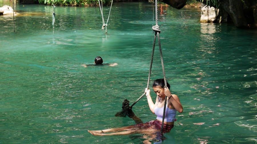 Địa hình độc đáo của đầm Blue Lagoon khiến dịch vụ các trò chơi mạo hiểm phát triển mạnh. Người Lào và du khách tham quan thường trải nghiệm ngồi ghế treo đung đưa, nhảy nhào lộn từ trên cao hoặc đu dây zip line đầy phiêu lưu. Trước khi đến đầm xanh này, lữ khách còn có thể tham quan quần thể động Poukham mênh mông xung quanh với sông núi hài hòa. Ảnh: CNN.