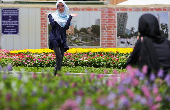 Hai cô gái đến từ Malaysia thích thú tạo dáng chụp ảnh bên những luống hoa nhiều loại.