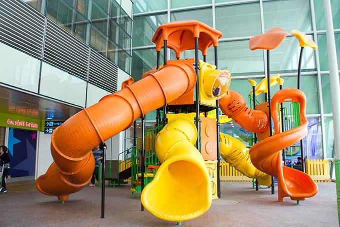 Cầu trượt sặc sỡ sắc màu đặt trong khu vui chơi trẻ em có các kích thước khác nhau. Có chiếc cao bằng vài tầng nhà dành cho người lớn.